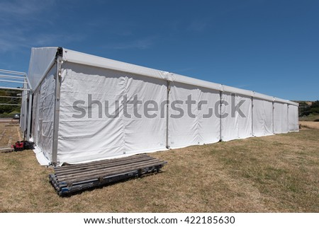 A large white tent in a grass field for parties and entertaining #422185630