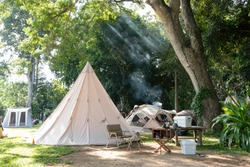 A large white traditional teepee tent with luxurious glamping interiorwith desk and chairs in forest,holidayvacation,Camping