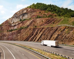 A large white trailer truck drives through a mountain pass with steep sedimentary rock to the sides of the road.