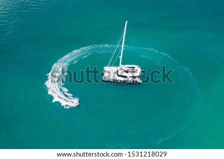 A large white yacht sailing in the warm azure ocean, next to which a small boat drifts, leaving waves behind. Sailing ships. Rest time. Photo from above. Dear vacation. Photo from a quadrocopter. #1531218029