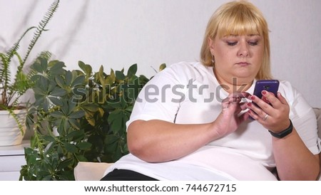 A large woman looks on smart phone and cries #744672715