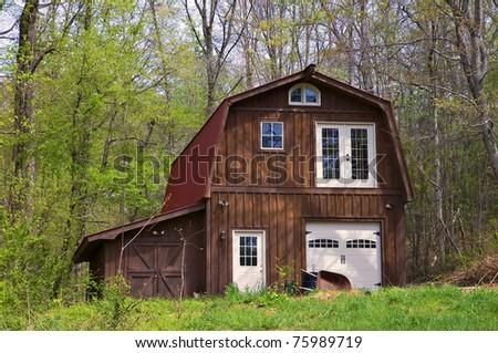 A large wooden barn with red metal roof designed to be used as a residence (if needed).