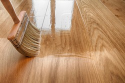 a large wooden brush covers the parquet with lacquer