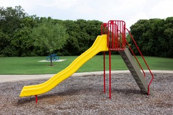 A large yellow and red slide at a playground area.