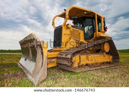 A large yellow bulldozer on a construction site near a farmers field
