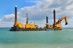 A large yellow excavator machine construct sea defencies on the beach
