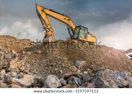 A large yellow excavator moving stone in a quarry