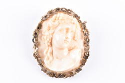 A late 19th century carved ivory cameo style brooch decorated with a carved profile of a Classical maiden, with grapes and vine leaves in her hair, within a stylised gilt metal mount