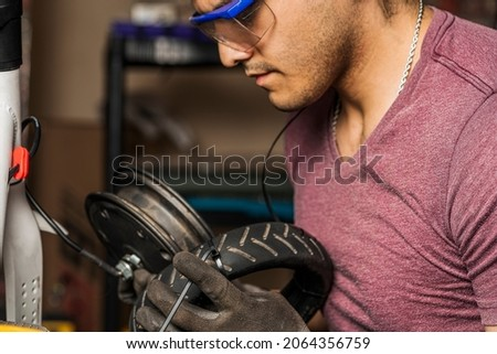 A latin mechanic man wearing safety goggles holding the tire and wheel rim of an electric scooter for replacement in his workshop.