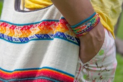 A Latino man wears a bag and decorative thread bracelets with Latin American and Central American designs.