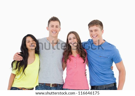 A laughing bunch of friends standing and holding each other as they all look into the camera
