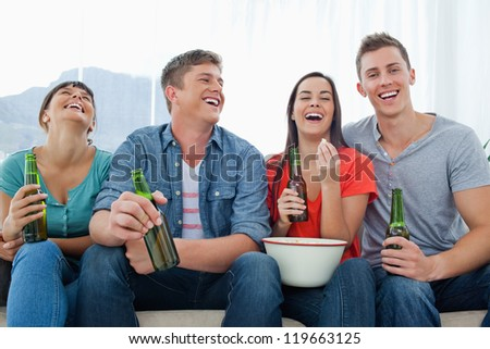 A laughing group of friends sitting with popcorn and beer as they have fun together
