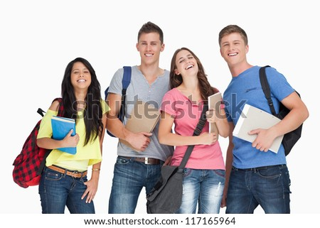 A laughing group of students with notepads and backpacks as they look at the camera