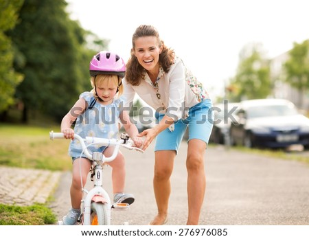 A laughing, smiling mother pushes her daughter forward on a warm summer\'s day as she teaches her how to ride her bicycle on a city sidewalk near a green park.