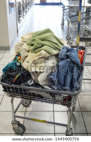 A laundry cart with laundry inside. #1449400796