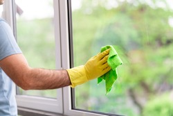 A laundry service worker in yellow rubber gloves and a blue T-shirt washes windows with green cloth. Window cleaning. Glass without stains. Space for text. The process of washing windows.
