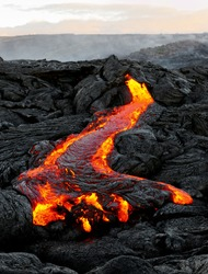 A lava flow emerges from a rock column and pours into a black volcanic landscape, in the background the first daylight - Location: Hawaii, Big Island, volcano