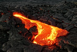 A lava flow emerges from a rock column and pours into a black volcanic landscape, the hot lava shows up in yellow and red shades - Location: Hawaii, Big Island, volcano