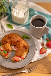 A lavish breakfast table setting - a cup of black coffee, milk, croissant sprinkled with almonds, slices of strawberries and green mint leaves. Light background. The look of a high angle.