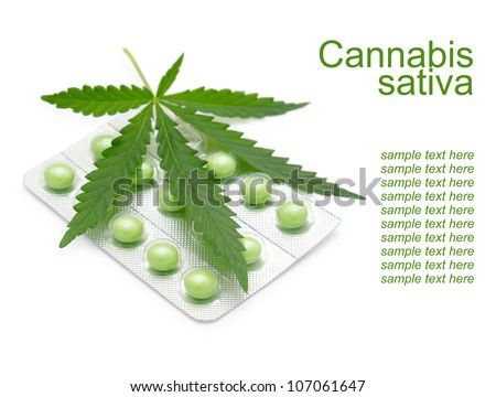 a leaf of marijuana (Cannabis sativa) on a blister with green drugs