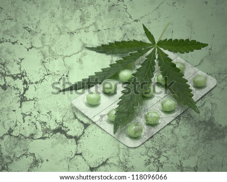 a leaf of marijuana (Cannabis sativa) on a blister with green drugs - grunge texture