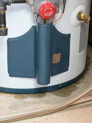 A leaking water heater, showing the regulator dial and pipe marked Water, sits in a utility room, with a puddle of water emerging from the bottom of it