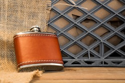 A leather covered stainless steel flask against a milkcrate and burlap.