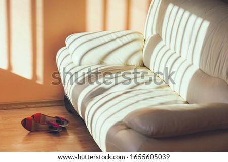 A leather sofa in the sun and shoes on the floor
