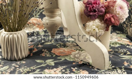 A leg of a white wooden table and a vase with flowers on a fabric with a floral pattern, a floral arrangement. #1150949606