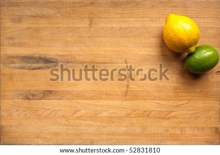 A lemon and a lime sit on a worn butcher block cutting board