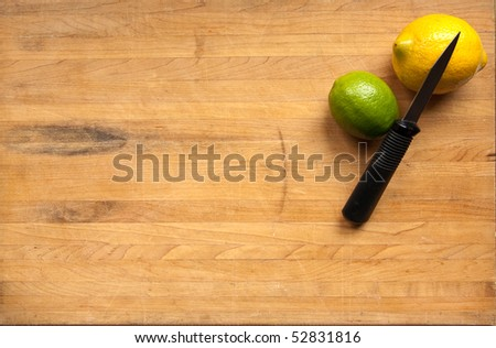A lemon and a lime sit waiting to be cut with a knife on a worn butcher block cutting board