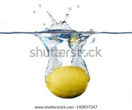 a lemon, falling to the water, with the splashing - stock photo