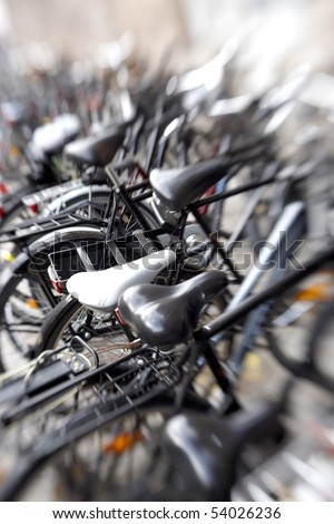 A lens blurred photo of lots of parked bikes. Useful as background.