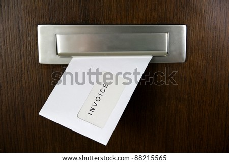 A letter in a letter box of a door with written INVOICE