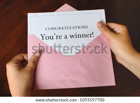 A letter that says Congratulations You're a winner! with female hands holding the open pink envelope  #1093597700