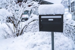 A letterbox with snow on top of it.