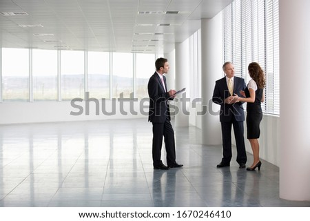 A letting agent showing businesspeople around an empty office Stock fotó ©