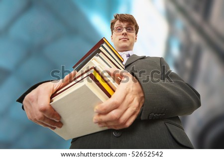 A librarian holding a big pile of books