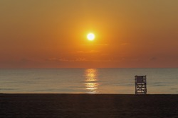 A lifeguard on the Myrtle beach surrounded by the sea during the sunset in South Carolina