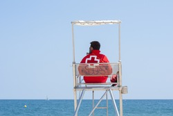 A lifeguard sitting on surveillance tower, front of the sea. / Lifeguard