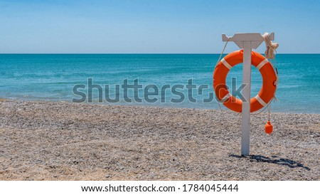 A lifeline on the red sea on the beach hangs on a bright sunny beach. Summer stand for salvation Stockfoto ©