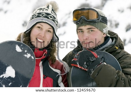 A lifestyle image of two young adult  snowboarders (series sport, mountains, extreme, horses, teenagers)