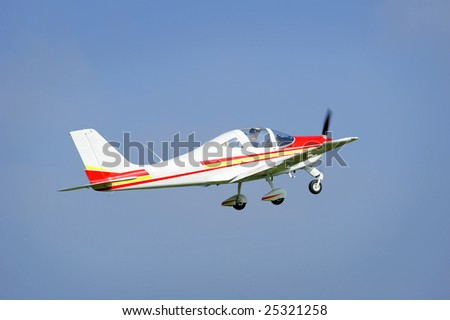 A light aircraft taking off into a clear blue sky.