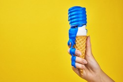a light bulb in a waffle cone in the hand of a girl with flowing blue paint