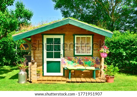A light green and wooden small shed, gardenhouse, with a bench some tools around it