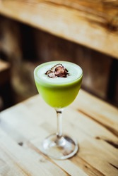 A light green sour tequila cocktail in a nick and nora glass, radish chips garnish, on a wooden table, 45 degrees angle shot