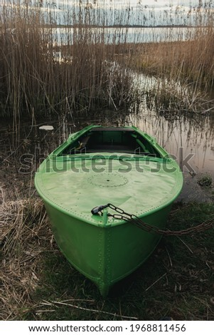A light green Soviet metal boat by the water of Lake Durbe is chained to the land with a rusty chain and lock. long dry reeds and grass. Blue clouds prims the storm. Sunny spring evening.  Stock foto ©