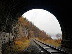 A light in the end of a tunnel. Inside an engineering structure made of stone on the Circum-Baikal Railway. Ionnel built at the beginning of the twentieth century