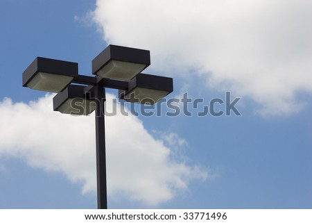 A 4-light lamp post against a blue sky and clouds.