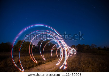 A light painting tunnel leading the way into a dark forest by the night.